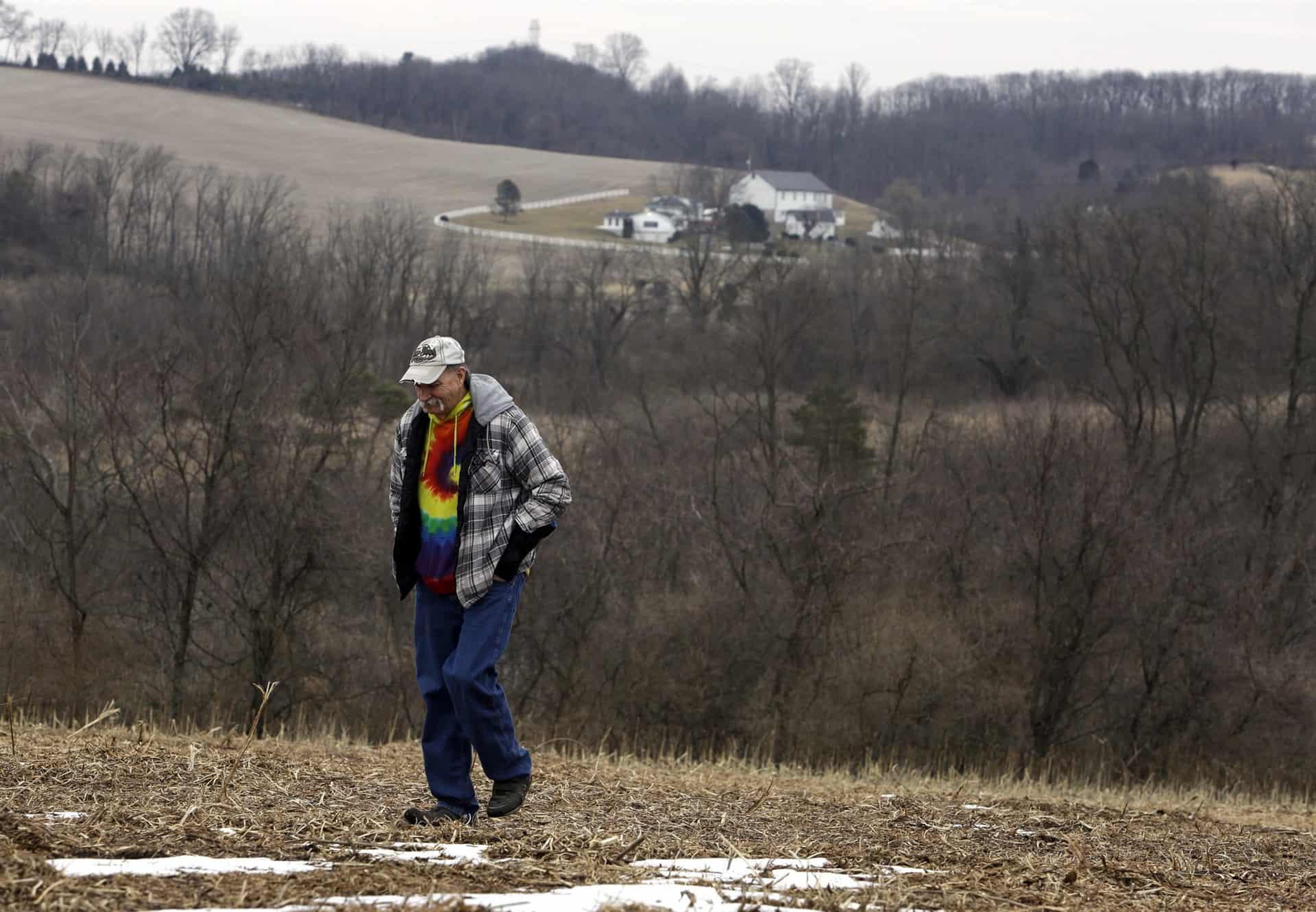 The uncle of Greg Longenecker, walks in the field where Longenecker was killed by a bulldozer in Bernville, Pennsylvania.