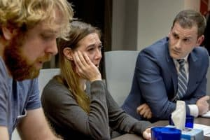Tom Minix and Kait Dowling crying, and their attorney, Jordan Strokovsky (right)