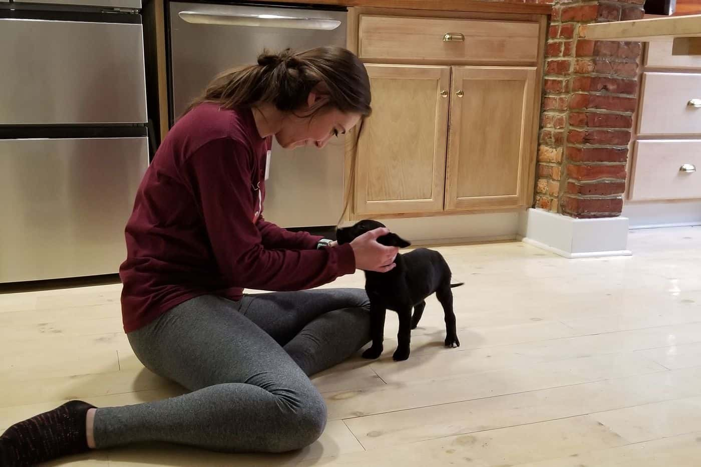 A young woman sits on her kitchen floor and rubs her tiny black puppy's ears